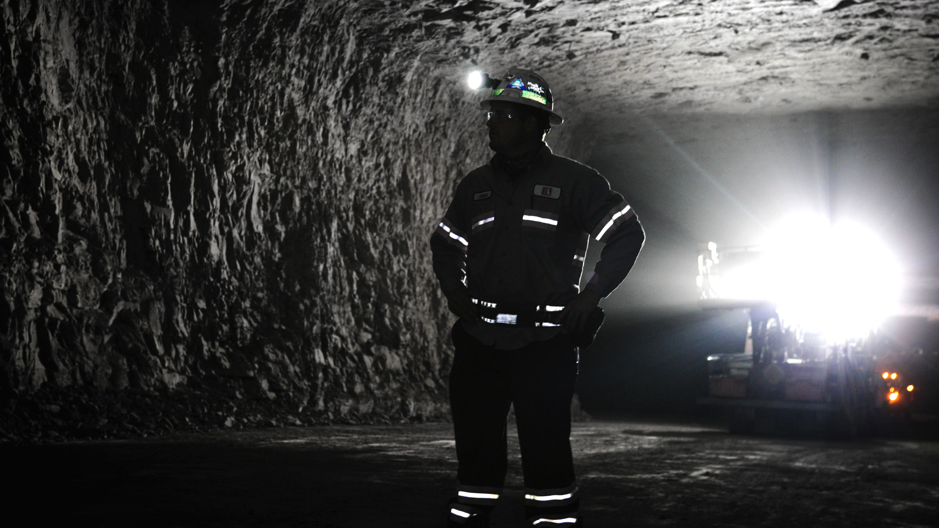 a man in safety gear and ppe in an underground mine