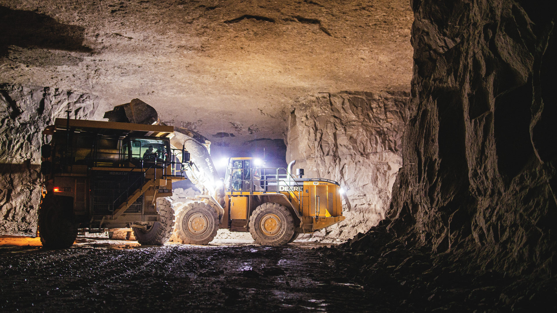 A loader dumping rock into a dump truck in an underground mine
